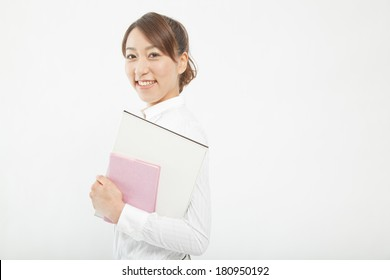 A Japanese businesswoman smiling with a document on her hand,