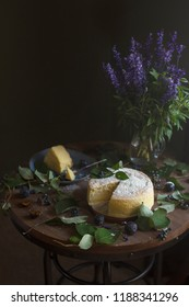 Japanese cheesecake with dark purple background, plums, rustic