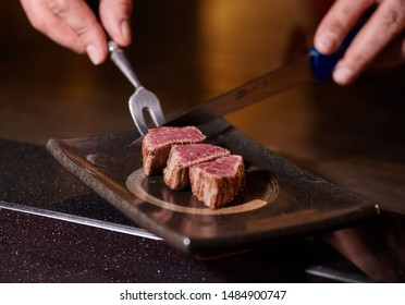 Japanese chef is cooking by hand a sliced delicious Kobe Beef or Wagyu steak in Teppanyaki style. Hot and delicious roast-beef, fesa, ranichi