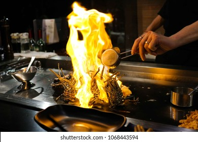Japanese Chef cooking lobster on a Teppanyaki grill with big flame