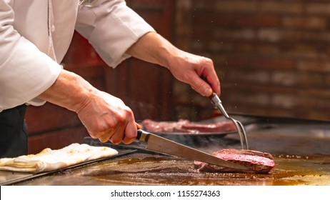 A Japanese chef hand holding a knife and fox is cooking a sliced Kobe Beef or Wagyu steak in pan in Teppanyaki style. It is hot and delicious. it is a famous Japanese beef steak.