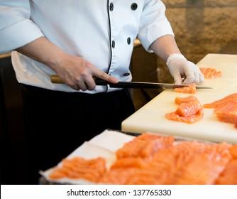 Japanese chef making sashimi in kitchen