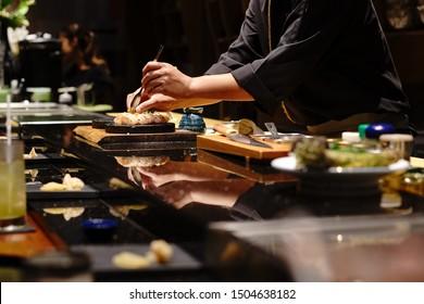 Japanese Chef making uni nigiri omakase style eating. Omakase style Japanese traditional.