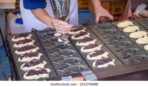 A Japanese chef pours batter into a giant waffle iron to make traditional fish-shaped cakes filled with sweet azuki red bean paste called 'taiyaki' ( 'grilled Japanese red seabream').