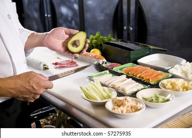 Japanese chef in restaurant with fresh ingredients for making sushi rolls