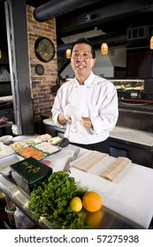 Japanese chef in restaurant with sushi ingredients ready to prepare rolls