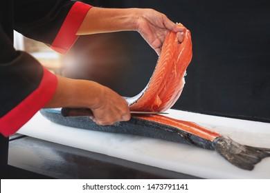 Japanese chef use sharp knife slicing raw fresh salmon fillet for sashimi, black background
