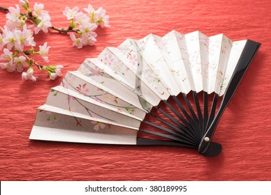 Japanese cherry twig and folding fan on the red background