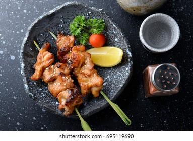 Japanese chicken grill or yakitori serve in izakaya style restourant set on Japanese style dish with flash lighting.
