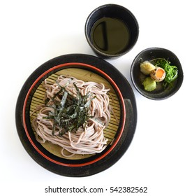 Japanese chilled soba noodles on black pot with quail egg and soy