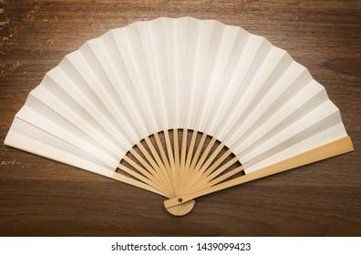 Japanese or chinese  folding fan on wood background