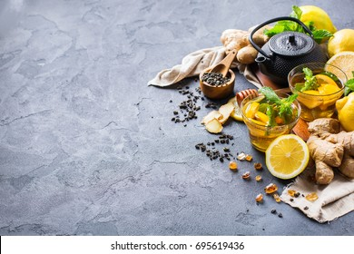 Japanese chinese tea teapot lemon ginger honey on a black table. Warm drink beverage infusion in glass for cold flu winter days, copy space background