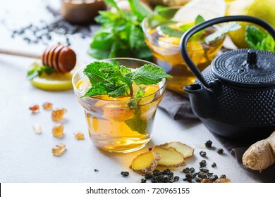 Japanese chinese tea teapot lemon ginger honey mint on a white table. Warm drink beverage infusion in glass for cold flu winter fall days