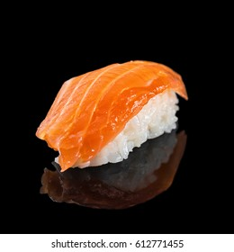 Japanese classic sushi nigiri with salmon isolated on black background with reflection, close up