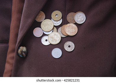 Japanese coins lay on brown jacket Business Travel Scholarship tax in Japan to donate money to help victims of natural disasters in Japan