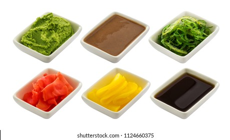 Japanese condiment for sushi. Soy sauce, wasabi, pickled ginger, chuka, sesame sauce and pickled radish isolated on white background