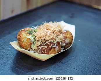 Japanese cook has made Takoyaki for tourist. Takoyaki is a ball-shaped Japanese snack made of a wheat flour-based batter and cooked in a special molded pan