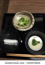 Japanese cooking example of kaiseki cooking with rice, miso and main dish served on black lacquer trays