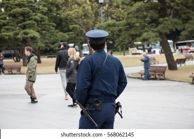 A japanese cop watching at the people can be seen in the picture. Few people and big trees can be seen in the image.