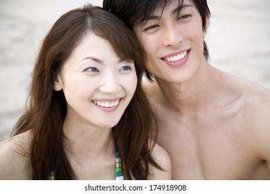 Japanese Couple cuddling on the beach