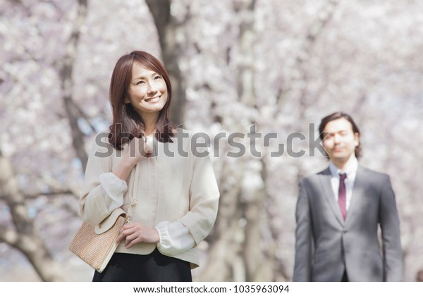 Japanese couple standing in row of cherry trees