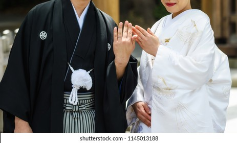 Japanese couple with traditional bride kimono and groom yukata uniform showing wedding rings by Closeup shot/