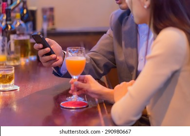 A Japanese couple using a smart phone at bar counter