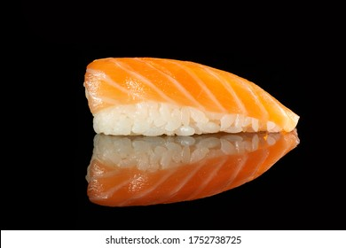 Japanese Cuisine - Appetizing Salmon Sushi Set, Nigiri. Philadelphia Sushi Roll - Maki Sushi with Philadelphia Cheese inside on mirror black background. Smoked salmon rolls served on a plate