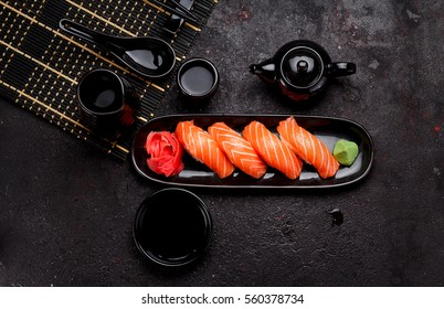 Japanese cuisine. Salmon sushi (nigiri) on a black plate and dark concrete background.