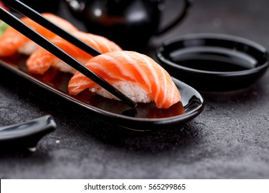 Japanese cuisine. Salmon sushi nigiri on a black plate with chopsticks.