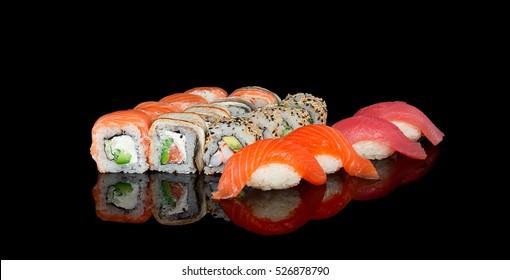 Japanese cuisine. Sushi over black background.