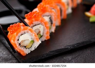 Japanese cuisine. Sushi over dark background.