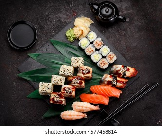Japanese cuisine. Sushi set on a stone plate and dark concrete background