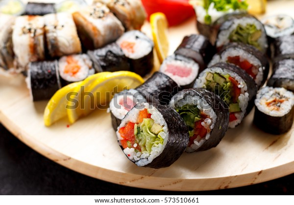 Japanese cuisine. Sushi set on a round wooden board over black concrete background.