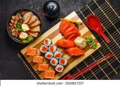Japanese cuisine. Sushi set and ramen soup over dark background.
