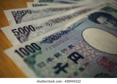 Japanese currency (yen) with its Asian symbols in the form bank notes on the wooden background