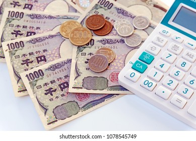 Japanese currency yen bank note with coin and calculator on white background.