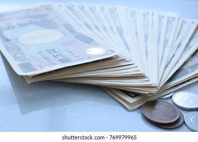 Japanese currency yen banknotes and coin on white tile.