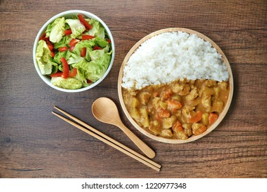 Japanese Curry rice (Kare) with meat, carrot,potato and mixed salad chili pepper.Close-up on a wooden plate and chopstick with spoon on wooden desk table.Horizontal top view.