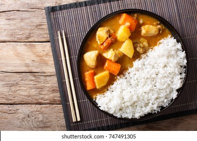 Japanese curry rice with meat, carrot and potato close-up on a plate on a table. horizontal top view from above