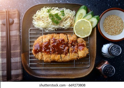 Japanese deep fried pork or tonkatsu with sauce fill on top in studio lighting.