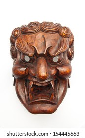 Japanese demon mask carving from wood isolated on white background