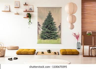 Japanese dining room interior with a tree poster, lamp, pillows and tatami mat with pot and cups on the floor
