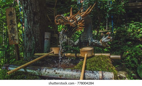 "A Japanese dragon fountain with sign that reads ""healing water""."