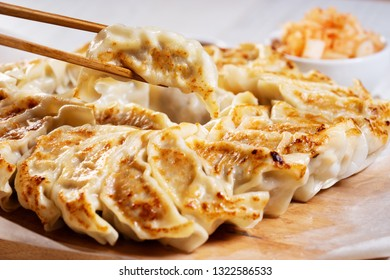 Japanese dumplings, gyoza with pork meat and vegetable stuff, with soy sauce and pickle side dish.