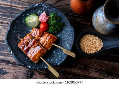 Japanese eel grilled in skewer or Unagi ibaraki set on plate in Japanese style with studio lighting