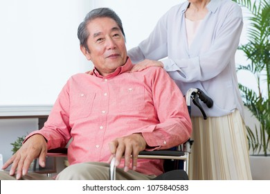 Japanese elderly couple pushing a wheelchair
