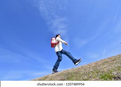 Japanese elementary school girl runnning in the blue sky