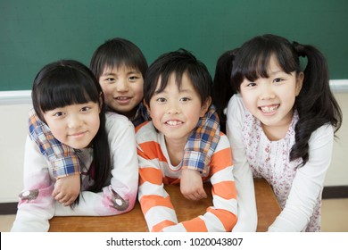 Japanese elementary school students standing in front of the blackboard