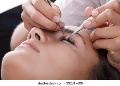 Japanese eyelash extensions. Long eyelashes. Beautiful dark-haired girl lies on a couch in the office of the master eyelash.